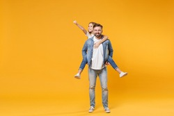Smiling bearded man with child baby girl. Father little kid daughter isolated on yellow background. Love family parenthood childhood concept. Give piggyback ride to joyful sit on back clenching fist