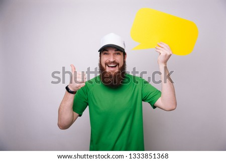 Smiling bearded man with speech bubble makes ok sign while standing on light gray background, portrait picture