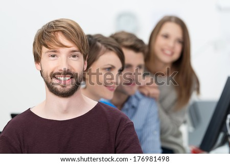 Smiling bearded young businessman posing looking directly at the camera while his colleagues work in the background