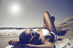 Smiling beautiful african woman lying on a beach in the sun