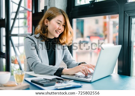 Smiling beautiful Asian girl with black hair working in cafe,Casual woman manager sitting in her office workspace with computer and big bright window and drinking coffee ,look at camera,vintage color