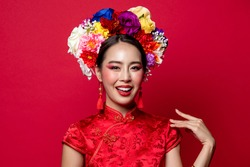 Smiling beautiful Asian woman in traditional oriental chinese style qipao dress with colorful make up and flowers on head in isolated red studio background