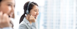 Smiling beautiful Asian woman working in call center office as a telemarketer