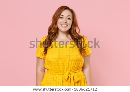 Smiling beautiful attractive young redhead plus size body positive chubby overweight woman in yellow casual dress posing looking camera isolated on pastel pink color wall background studio portrait Photo stock ©
