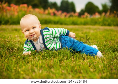 Smiling beautiful baby looking at camera outdoors in sunlight