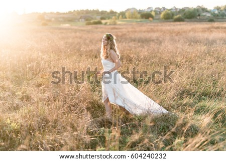 Smiling beautiful bride wearing a natural flower wreath and standing in the golden summer fields. #604240232