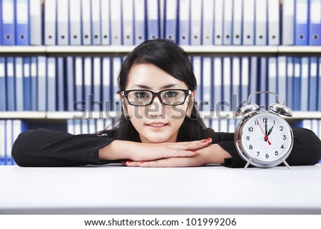 Smiling beautiful businesswoman with alarm clock, shot in the office