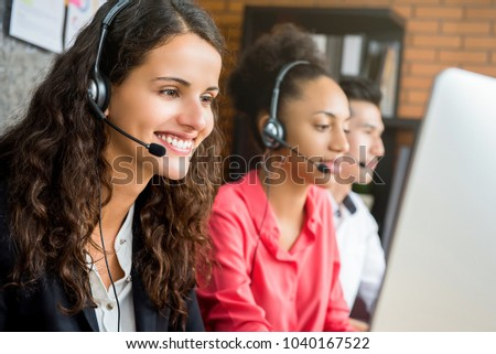 Smiling beautiful businesswoman working in call center as a telemarketing operator with her international team