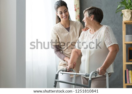 Smiling beautiful caregiver and disabled old lady with walker at home