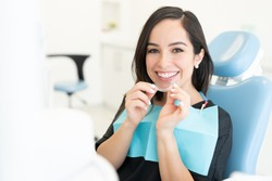 Smiling beautiful Caucasian mid adult woman holding invisible orthodontic retainer