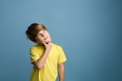 Smiling beautiful child thinking and looking upward. Portrait of child on colored blue background
