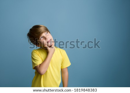 Photo of  Smiling beautiful child thinking and looking upward. Portrait of child on colored blue background