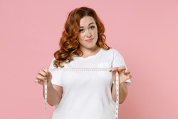 Smiling beautiful confused young redhead plus size body positive woman 20s wearing white casual t-shirt hold measure tape looking camera isolated on pastel pink color wall background studio portrait