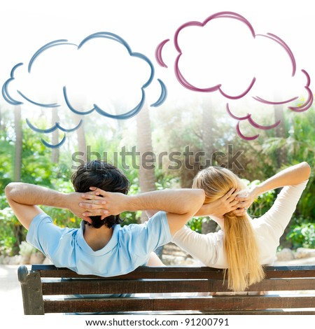 Smiling beautiful couple sitting on a bench at summer park and dreaming about something