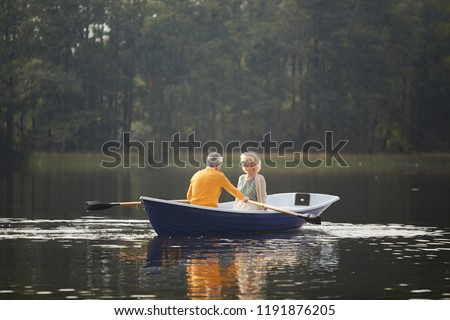 Smiling beautiful curly-haired senior lady in cardigan sitting on boat and talking to boyfriend while he rowing oars