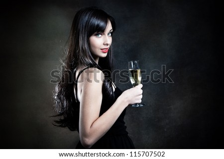 smiling beautiful elegant young woman with glass of champagne studio shot