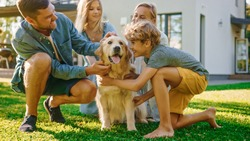 Smiling Beautiful Family of Four Posing with Happy Golden Retriever Dog on the Backyard Lawn. Idyllic Family Cuddling Loyal Pedigree Dog Outdoors in Summer House Backyard.