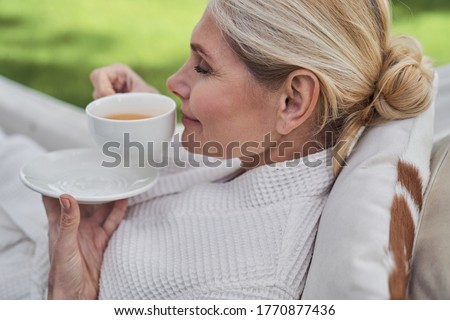 Smiling beautiful female is drinking mug of hot beverage while relaxing in hammock in open air