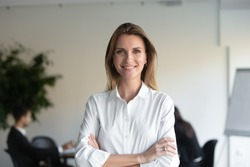 Smiling beautiful female professional manager standing with arms crossed looking at camera, happy confident business woman corporate leader boss ceo posing in office, headshot close up portrait