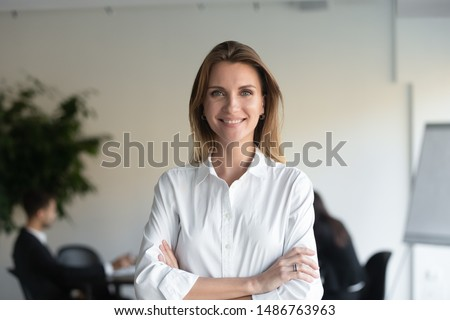 Smiling beautiful female professional manager standing with arms crossed looking at camera, happy confident business woman corporate leader boss ceo posing in office, headshot close up portrait stock photo