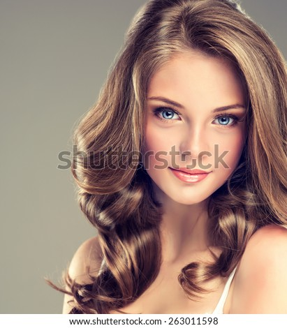 Smiling Beautiful girl brown hair with an elegant hairstyle , hair wave ,curly