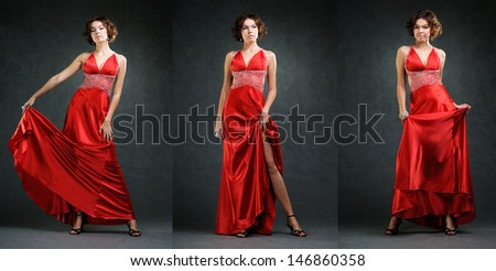 Smiling beautiful girl in long red dress posing in studio on grey background.