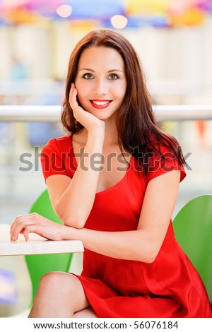 Smiling beautiful girl in red dress sits at table in cosy cafe.