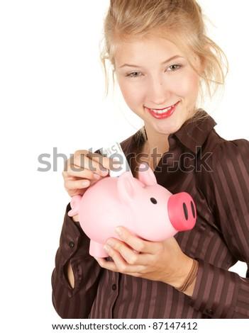 smiling beautiful girl putting five euro in piggy bank