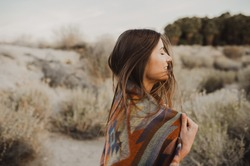 Smiling, beautiful hipster traveler girl in gypsy look and windy hair, in desert nature.  Artistic photo of young hipster traveler girl in gypsy look, in Coachella Valley in a desert valley in Souther