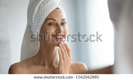 Smiling beautiful lady apply skincare cream on face look in bathroom mirror, happy young woman wrap towel on head put facial creme on doing morning healthy skin care beauty routine treatment concept