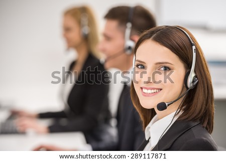 Smiling beautiful lady working at call center with colleagues in office. #289117871
