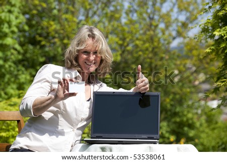 smiling beautiful mature blond woman with laptop and businesscard posing thumbs up