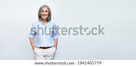 Smiling beautiful mature business woman standing isolated on white background. Older senior businesswoman, 60s grey haired lady professional female ceo, coach looking at camera, banner, copy space.