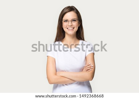 Smiling beautiful millennial girl wear glasses and white t-shirt stand with arms crossed isolated on grey studio background, happy young woman in spectacles look at camera posing or casting