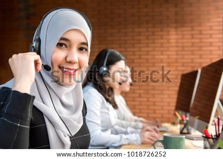 Smiling beautiful Muslim businesswoman telemarketing agent or customer service operator working in call center company with her team