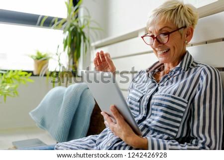 Smiling beautiful senior woman using digital tablet at home