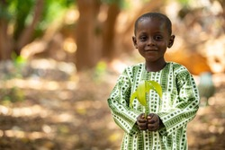 Smiling beautiful small African kid, dressed in a traditional outfit, holding a mango seedling in a shaded tree area in a suburb of Niamey, capital of Niger
