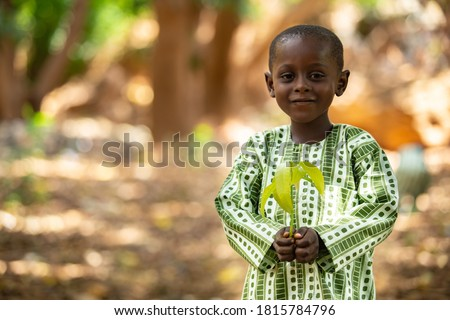 Smiling beautiful small African kid, dressed in a traditional outfit, holding a mango seedling in a shaded tree area in a suburb of Niamey, capital of Niger Stock photo ©
