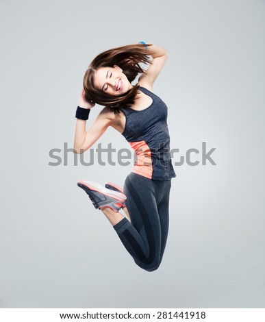 Smiling beautiful sports woman jumping over gray background