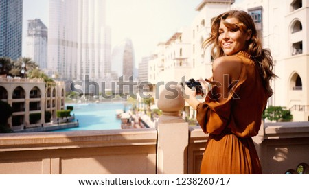 Smiling beautiful tourist woman portrait with camera in Dubai.