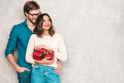 Smiling beautiful woman and her handsome boyfriend. Happy cheerful family posing in studio near gray wall. Valentine's Day. Models hugging and giving his girlfriend gift box. Christmas, x-mas, concept