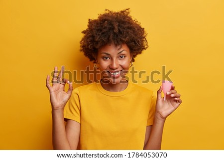 Smiling beautiful woman approves using menstrual cup, makes okay gesture and holds silicone product to insert into vagina in hand gives recommendations for women begginer cup users isolated on yellow