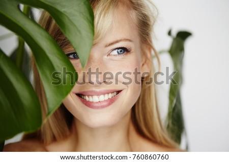Smiling beautiful woman behind leaf, looking away Stock photo ©