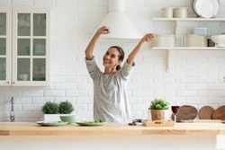 Smiling beautiful woman dancing in modern kitchen, preparing healthy food alone, cooking salad, carefree happy girl singing and moving to favorite music, having fun at home, enjoying leisure time