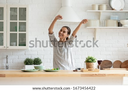 Smiling beautiful woman dancing in modern kitchen, preparing healthy food alone, cooking salad, carefree happy girl singing and moving to favorite music, having fun at home, enjoying leisure time