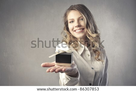Smiling beautiful woman holding a small gift - stock photo