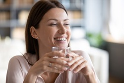 Smiling beautiful woman holding glass of pure mineral water close up, satisfied happy young female with perfect skin looking in distance, healthy lifestyle and natural beauty concept, dehydration