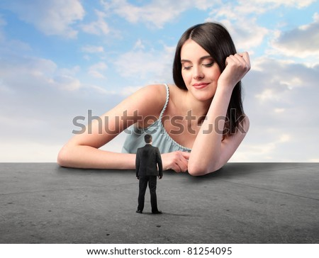 Smiling beautiful woman looking at a tiny businessman