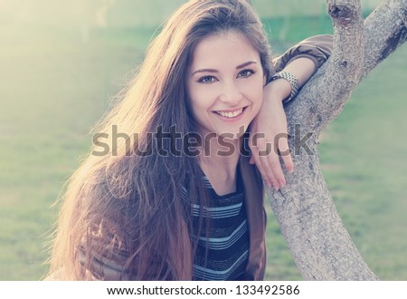 Smiling beautiful woman near tree outdoors summer background looking happy