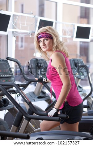 Smiling beautiful woman on trainer machine in sport gym